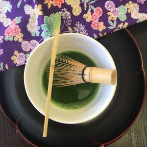 A bowl of Matcha tea with a chashaku and chasen