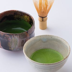 Two bowls of matcha tea with a whisk